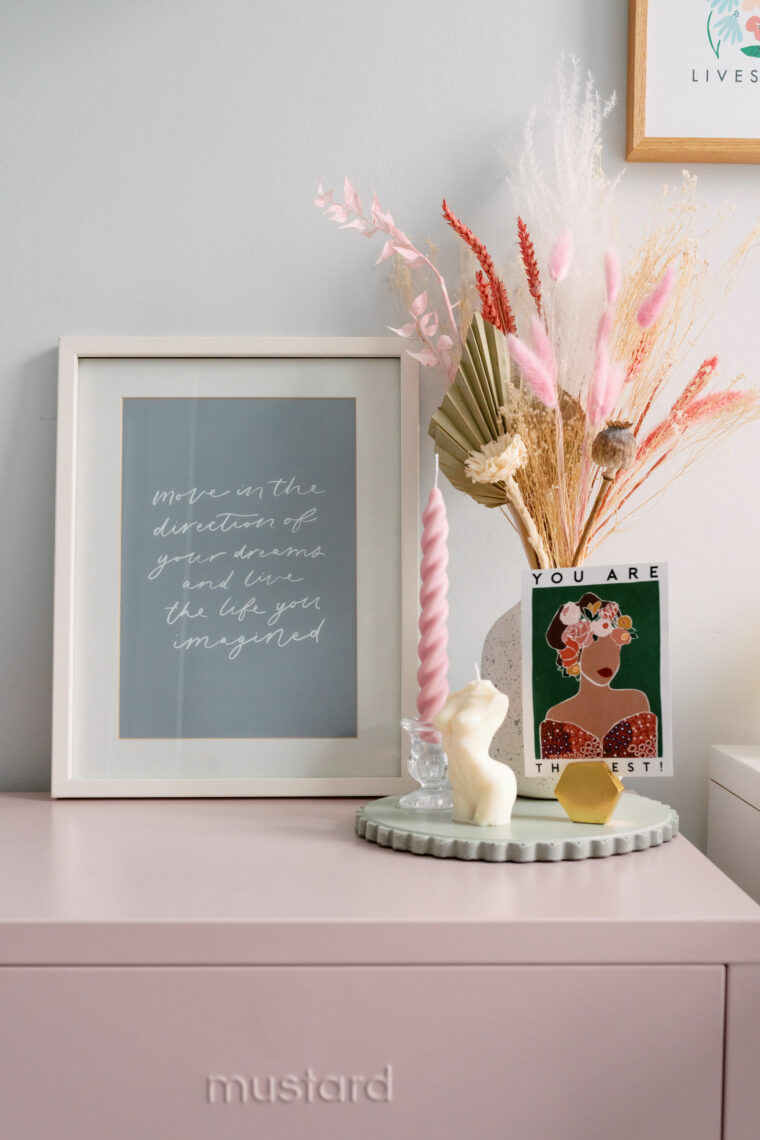 Blush pink mustard locker with print on top, candles and dried flowers